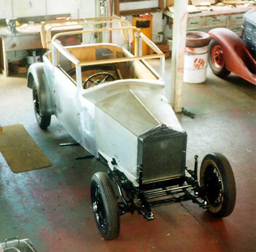 View of bare metal body sitting on restored chassis